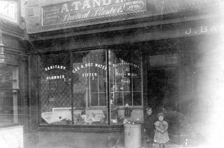 Tandy's shop in Swan Street, Warwick. with sign for sanitary, plumbers, gas,painting and wall hanging supplies. Two children standing at the entrance. 1920's  |  IMAGE LOCATION: (Warwickshire County Record Office)