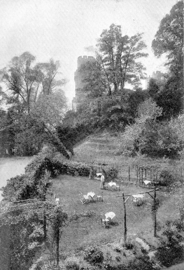 Tower tea gardens on the banks of the River Avon with Warwick Castle tower in the background.  1910s |  IMAGE LOCATION: (Warwickshire County Record Office)