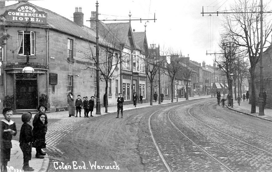 The Crown Commercial hotel and shops in Coton End, Warwick. A group of children are standing in the foreground.  1910s |  IMAGE LOCATION: (Warwickshire County Record Office)