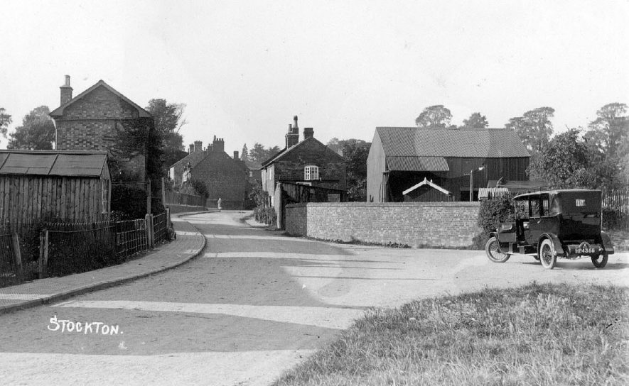 Road, showing houses, cottages and farm buildings; taxi in foreground (Reg. HP 4358. Hackney Carriage no.6).  Postmark 1930s