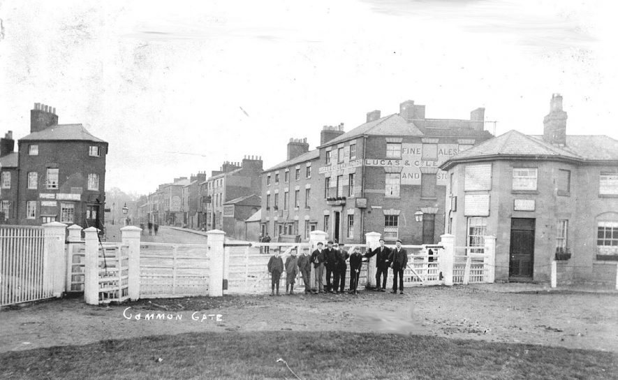 Common Gate entrance to Warwick racecourse with a group of young men standing at the gates.  1900s |  IMAGE LOCATION: (Warwickshire County Record Office)