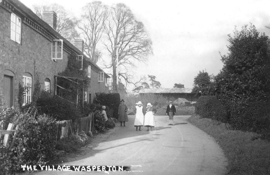 A village view of terraced houses and people standing in the road at Wasperton.  1920s |  IMAGE LOCATION: (Warwickshire County Record Office)