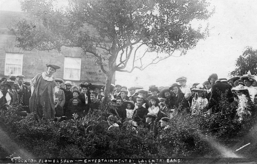 'Stockton Flower Show - entertainment by Daventry Band' (band not shown); shows the audience, some in fancy dress.  Postmark 1907 |  IMAGE LOCATION: (Warwickshire County Record Office)