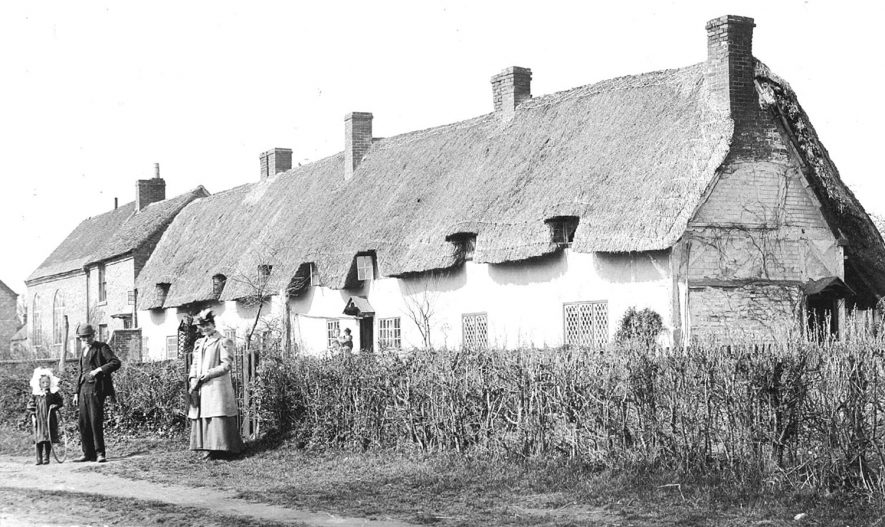 Row of thatched and half timbered cottages with the chapel in the background and a man, woman and child with hoop in the foreground. Welford on Avon.  1900s |  IMAGE LOCATION: (Warwickshire County Record Office)