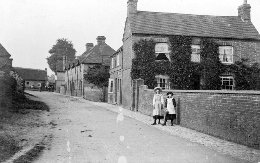 The High Street looking north east from The Square and showing The Crown Inn with two girls in the foreground.  1900s |  IMAGE LOCATION: (Warwickshire County Record Office)