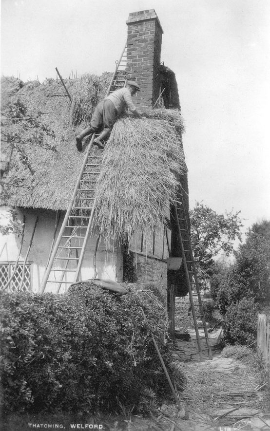 A man thatching a cottage in Welford on Avon.  1920s |  IMAGE LOCATION: (Warwickshire County Record Office)