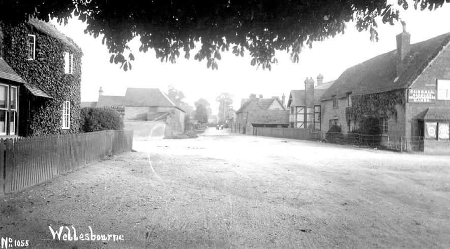 Part of Church Street looking towards School Road, showing Currall, saddler and harness maker on the right, Wellesbourne.  1910s    IMAGE LOCATION: (Warwickshire County Record Office)
