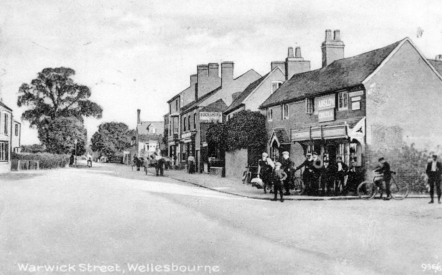 View of Warwick Street (now Warwick Road), Wellesbourne. A group of men and boys are standing on the corner of the street.  1910s |  IMAGE LOCATION: (Warwickshire County Record Office)