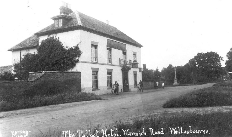 The Talbot Hotel, situated on the corner of the Warwick Road and Bridge Street, Wellesbourne.  The girl with the bicycle was Christine Oldham (later Grantham).  1920s |  IMAGE LOCATION: (Warwickshire County Record Office) PEOPLE IN PHOTO: Oldham, Christine, Oldham as a surname