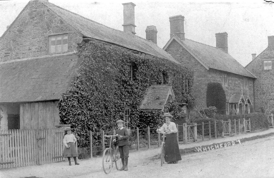 Cottages in Whichford. Young girl; boy and woman with bicycles. 1900s |  IMAGE LOCATION: (Warwickshire County Record Office)