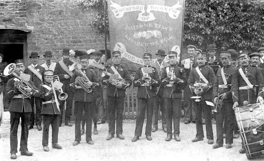 The Sibford Band posing before a banner of  the Whichford branch of the Tysoe Insurance Society at Whichford.  1900s |  IMAGE LOCATION: (Warwickshire County Record Office)