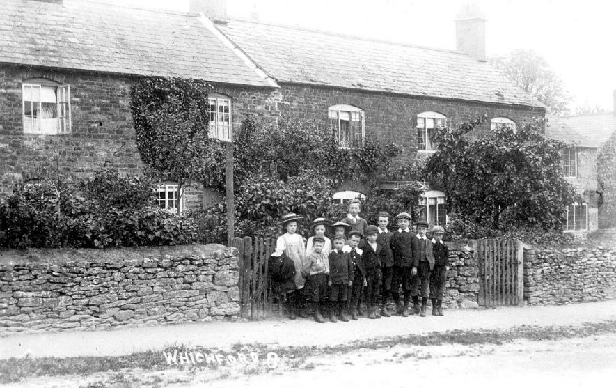 A group of schoolchildren in front of cottages, Whichford.  1900s |  IMAGE LOCATION: (Warwickshire County Record Office)