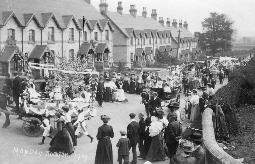 May Day procession of decorated carts with children in fancy-dress passing Victoria Terrace, Stockton. Crowd of people watching.  C.1910 |  IMAGE LOCATION: (Warwickshire County Record Office) IMAGE DATE: (c.1909)