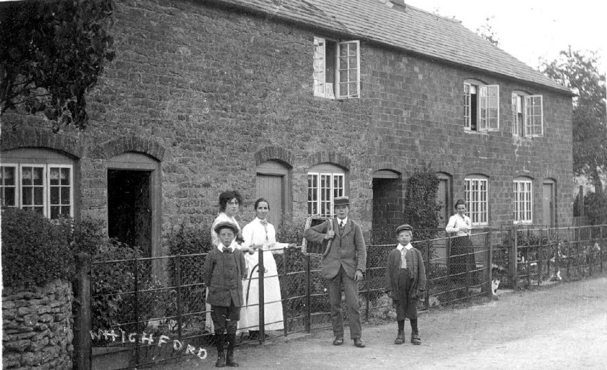 Cottages with young people and boys, one with delivery basket in Whichford.   1910s    IMAGE LOCATION: (Warwickshire County Record Office)