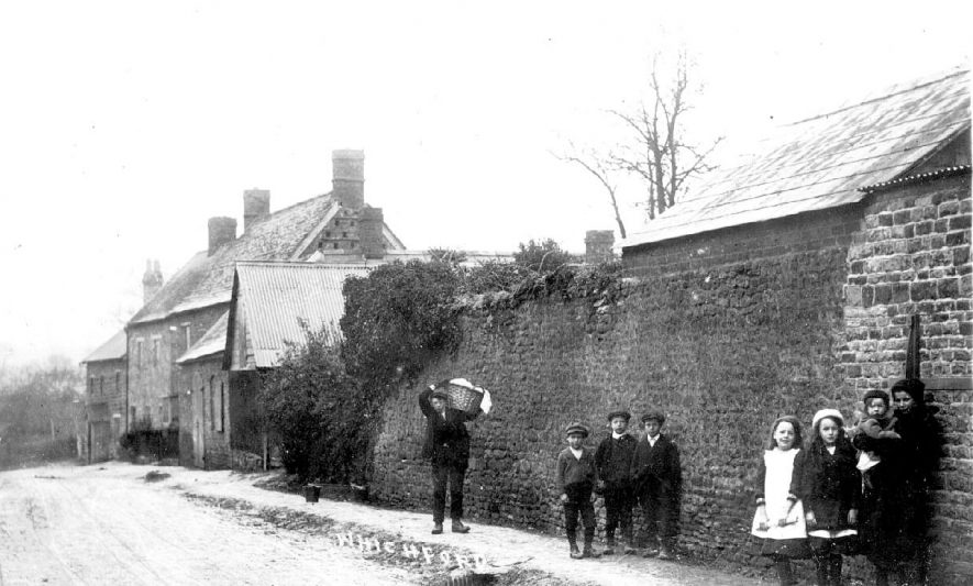 Village street with cottages, children and young man carrying a wicker basket. Whichford.  1900s |  IMAGE LOCATION: (Warwickshire County Record Office)