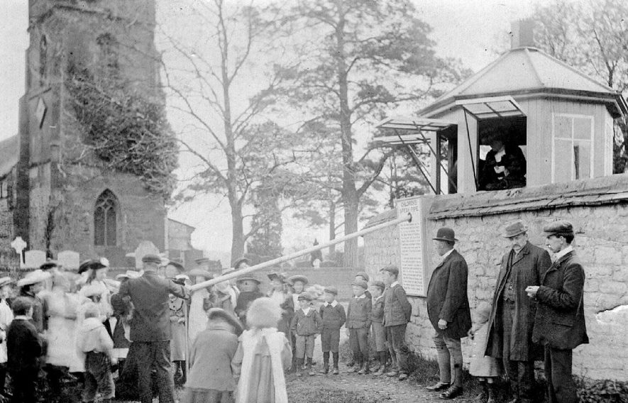 Crowds gathered round the Children's' Speak Pipe at St Michael's church, Stockton.  This pipe extended through the rectory garden wall to a summer house where the Rector, Revd Thomas Colley,  would sit.  Children were encouraged to speak religious sayings up it in exchange for a penny in an orange or an apple which was rolled down to them.  1900s |  IMAGE LOCATION: (Warwickshire County Record Office)