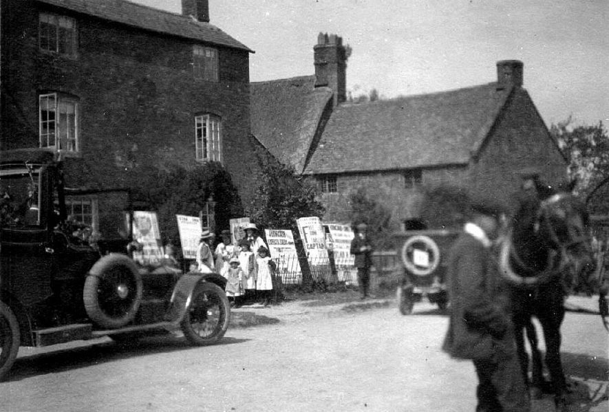 Election posters, people, and cars in a Warwickshire village during the election campaign for Malcolm Kincaird-Smith, Liberal M.P. for Stratford upon Avon, 1906-9. |  IMAGE LOCATION: (Warwickshire County Record Office)