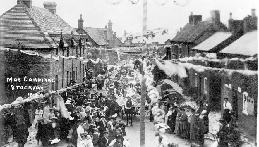 May Day procession moving along a highly decorated High Street, Stockton.  A Maypole can be seen in the foreground.  1913 |  IMAGE LOCATION: (Warwickshire County Record Office)