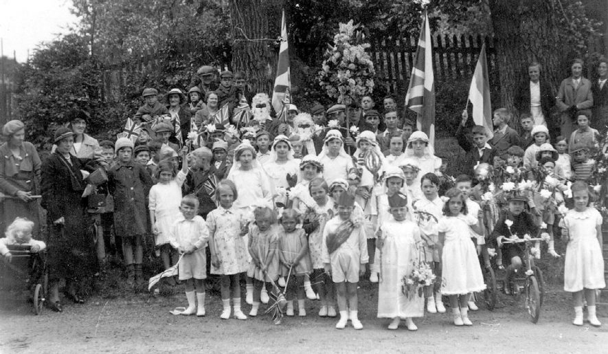 Group of children in fancy dress with some adults celebrating Empire Day,  Whitnash.  1920s. [Images of England -Whitnash by Jean Field Pages 62/63 describes the scene as May Day Celebrations 22nd May 1936.] |  IMAGE LOCATION: (Warwickshire County Record Office)