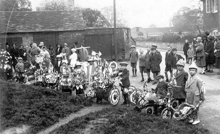 Group of children with decorated bicycles, prams etc. and other children and adults looking on, celebrating the Prince of Wales visit to Leamington Spa.  1924 |  IMAGE LOCATION: (Warwickshire County Record Office)