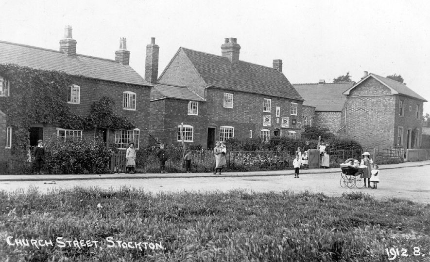 Church Street, shows clothes/shoe shop; adults and children, one with pram, standing in the road.  1912 |  IMAGE LOCATION: (Warwickshire County Record Office)