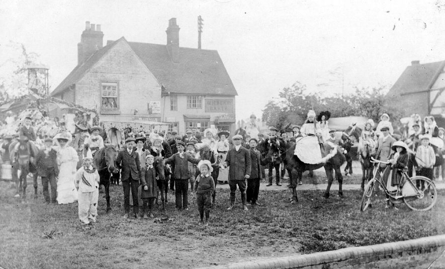 Large group of men, women and children - some in fancy dress - on the village green in Wolston. In the background is the baker's shop belonging to William Berry.  1900s |  IMAGE LOCATION: (Warwickshire County Record Office)