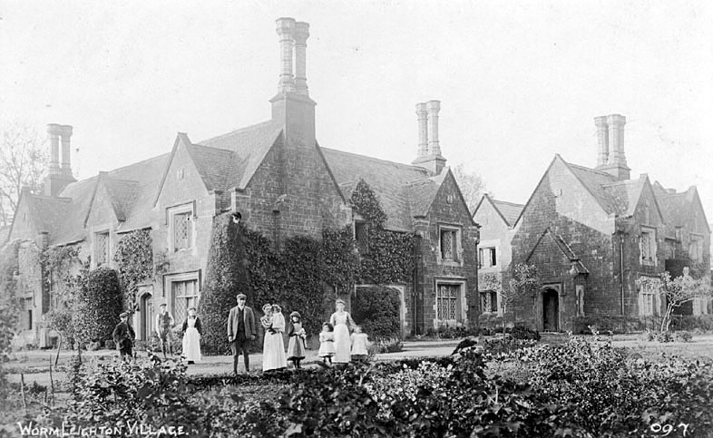 A family group posing outside estate cottages, Wormleighton.  1900s |  IMAGE LOCATION: (Warwickshire County Record Office)