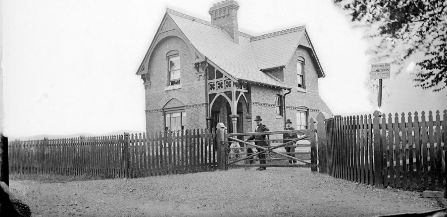 The cemetery lodge, Nuneaton.  Two men in top hats standing by the gate, one of whom is carrying a spade.  1900s |  IMAGE LOCATION: (Warwickshire County Record Office)