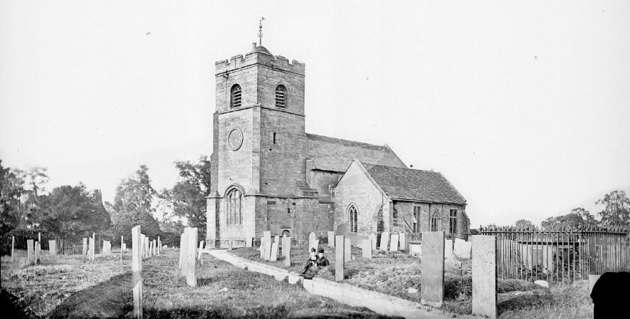 The church and graveyard St Chilvers Coton, with two ladies sitting.  1900s |  IMAGE LOCATION: (Warwickshire County Record Office)