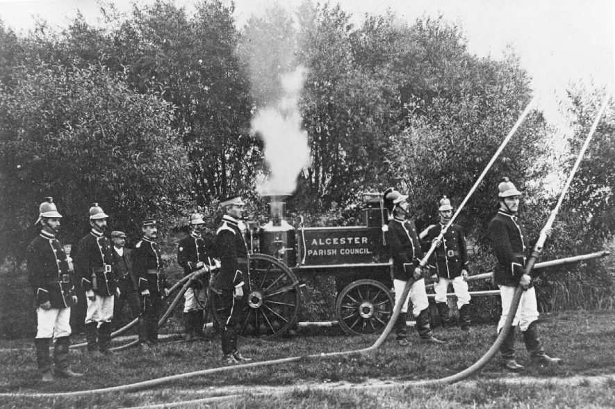 First steam fire engine c.1902, showing firemen with water hoses.  Alcester Parish Council written on the side of the fire engine. |  IMAGE LOCATION: (Warwickshire County Record Office) IMAGE DATE: (c.1902)