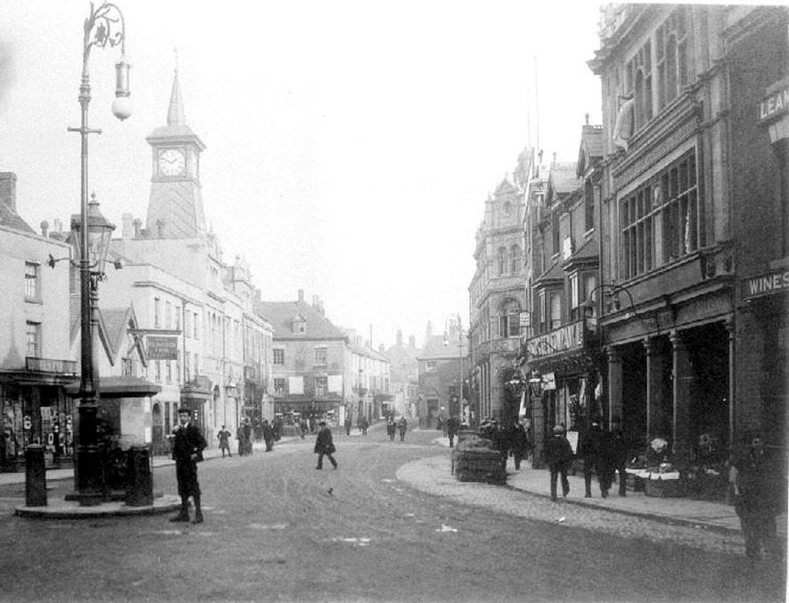Market Place, Nuneaton, showing traffic island with gas and electric lights, Star Tea Company shop, The Peacock Inn and Jeffcoats. Prior to 1907 because Boots The Chemist was built then. See also PH(N) 759/104/2. |  IMAGE LOCATION: (Warwickshire County Record Office)
