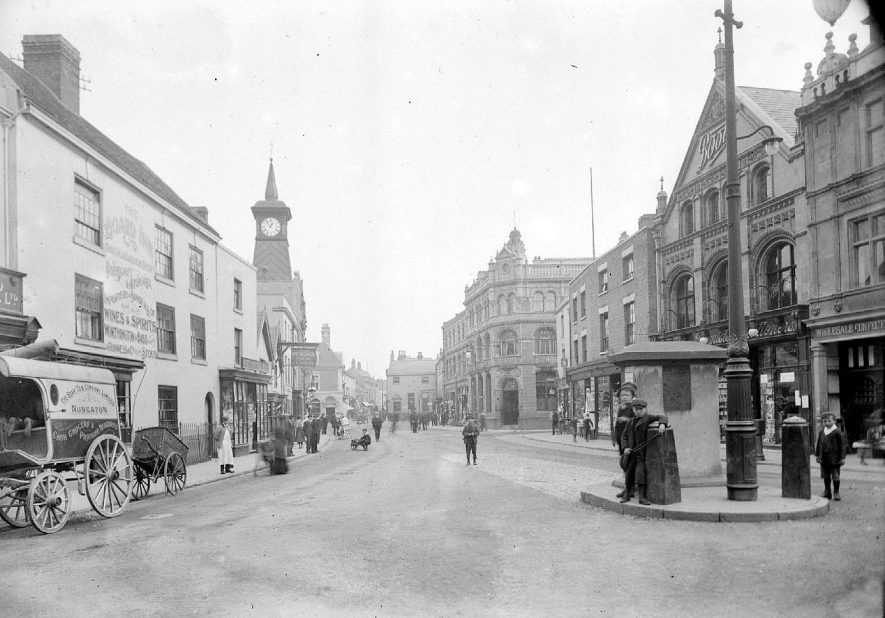 Market Place, Nuneaton, showing traffic island with gas light removed (see PH(N) 759/104/1). Also showing The Board Inn, Winfield grocers, The Counties Bank, Boots The Chemist. The Peacock Inn ( T.F. Hadley ), W.H. Hope, milliners. Also a cart of The Star Tea Company Ltd.  1910s |  IMAGE LOCATION: (Warwickshire County Record Office)
