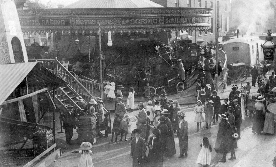 Alcester Mop, showing fairground equipment and crowds.  c.1910 |  IMAGE LOCATION: (Warwickshire County Record Office) IMAGE DATE: (c.1910)