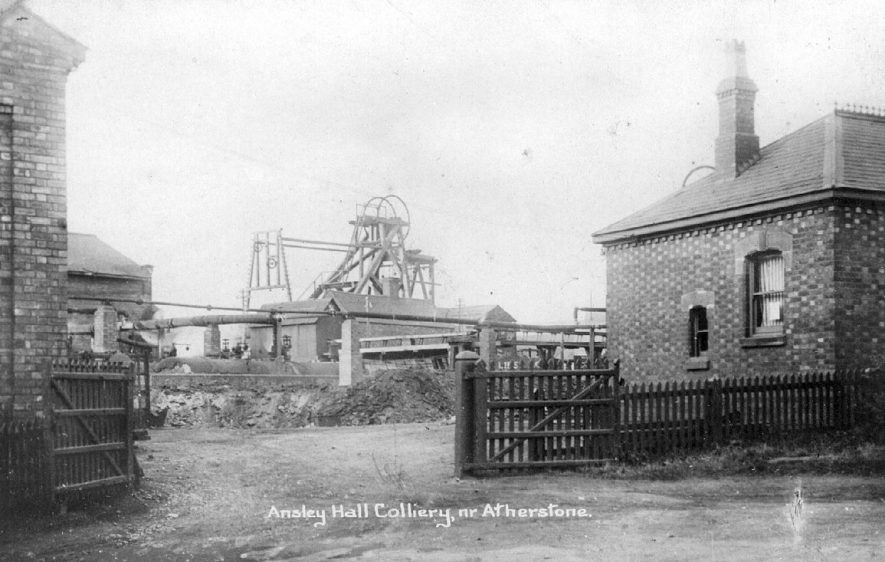 Entrance to Ansley Hall Colliery with pit head winding gear in the background.  1900s |  IMAGE LOCATION: (Warwickshire County Record Office)