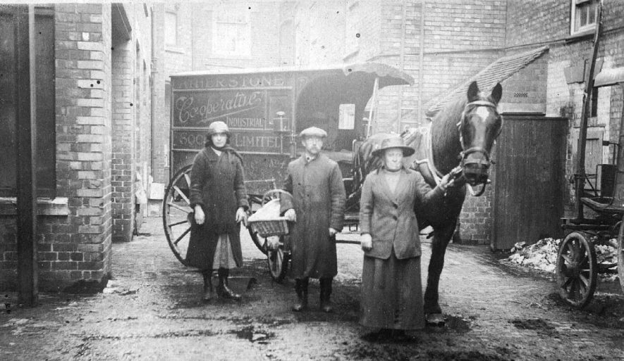 Atherstone Co-operative Society delivery cart with horse in yard, man & two  women standing beside it.  1900s |  IMAGE LOCATION: (Warwickshire County Record Office)
