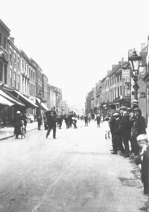 Long Street, Atherstone, showing pedestrians and shops. Red Lion Hotel on right.  1920s |  IMAGE LOCATION: (Warwickshire County Record Office)
