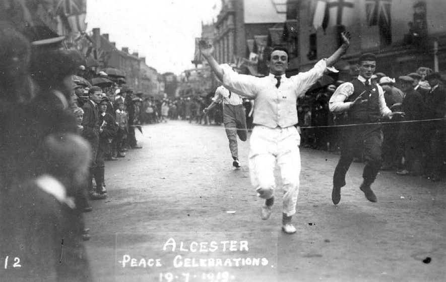 Racing in Alcester High Street during the Peace Celebrations of 19 July 1919, watched by a large crowd. |  IMAGE LOCATION: (Warwickshire County Record Office)