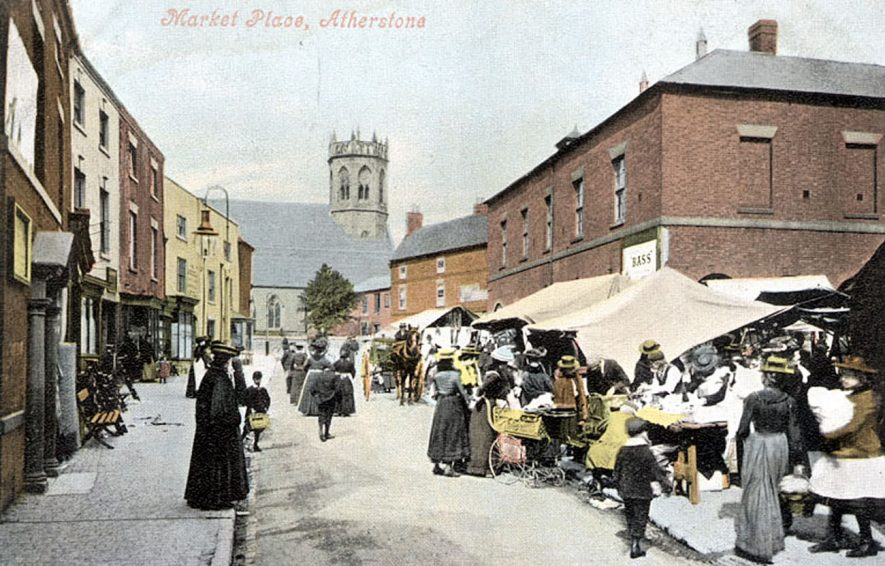 Tinted photograph of Atherstone Market Place with stalls and shoppers, children, perambulator and horse and cart.  1900s |  IMAGE LOCATION: (Warwickshire County Record Office)