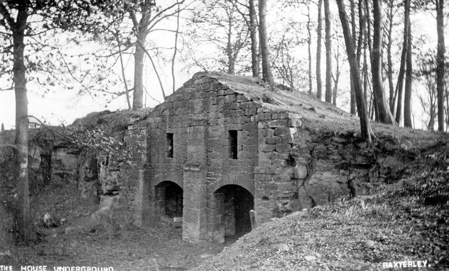 Stone building with two entrance arches, partly underground in Baxterley. It is thought that the original use was as a smoke house to smoke meat and could fit in as many as 50 cows!  1900s |  IMAGE LOCATION: (Warwickshire County Record Office)