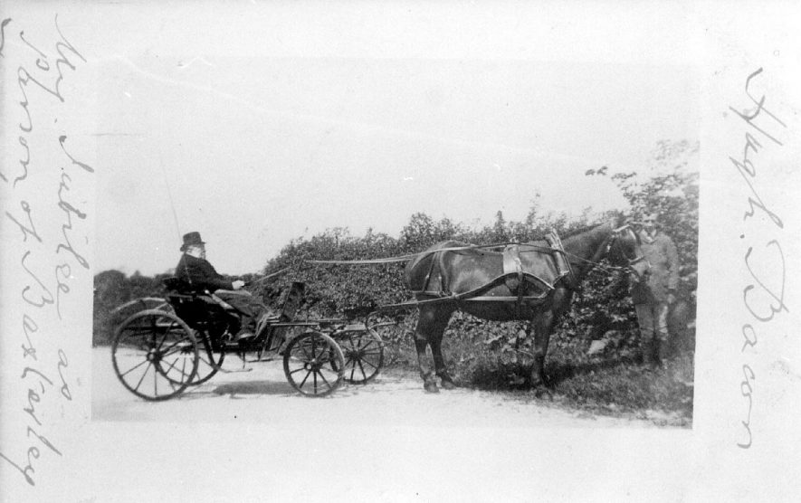 The Rev. Hugh Bacon, Rector of Baxterley, in a small horse -drawn carriage at Baxterley.  Boy at horse's head.  Inscribed