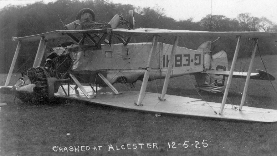 A crashed biplane on its back in a field, Alcester.  1925 |  IMAGE LOCATION: (Warwickshire County Record Office)