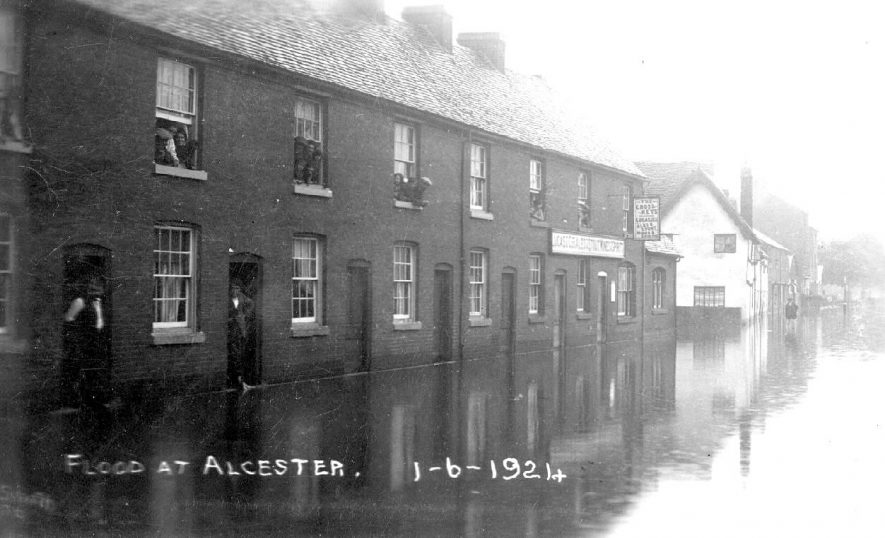 A flooded street in Alcester showing the Cross Keys public house. People viewing from first floor windows and doorways of terraced houses. 1 June 1924. |  IMAGE LOCATION: (Warwickshire County Record Office)