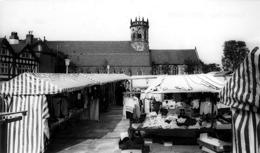Atherstone market day with stalls and items for sale with the Parish Church in background.  1960s |  IMAGE LOCATION: (Warwickshire County Record Office)