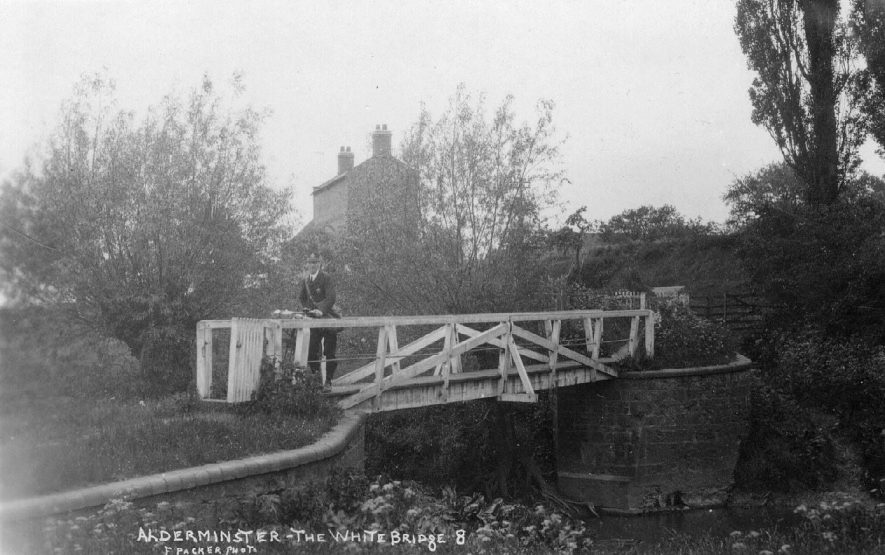 The White Bridge, Alderminster, showing the postman with bicycle crossing wooden bridge and a house in the background.  1920s |  IMAGE LOCATION: (Warwickshire County Record Office)