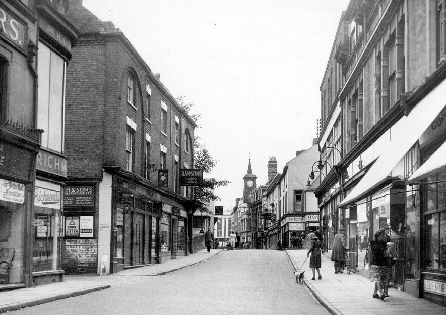 Bridge Street, Nuneaton. Various shops; and part of a sign for a circulating library.  1950s |  IMAGE LOCATION: (Warwickshire County Record Office)