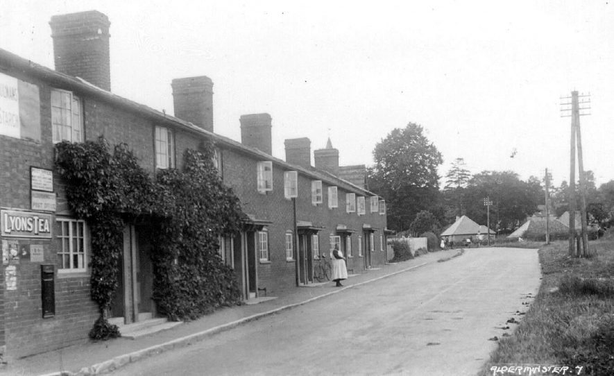 A street in Alderminster showing post office in foreground. Bicycle leaning against wall of house, woman standing nearby. Other people in distance.  1920s |  IMAGE LOCATION: (Warwickshire County Record Office)