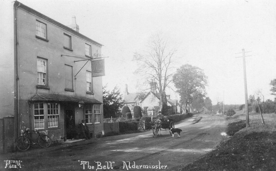 The Bell Inn, Alderminster, with people in doorway, bicycle leaning against wall and pony and trap with man and dog approaching. Houses in background.  1920s |  IMAGE LOCATION: (Warwickshire County Record Office)