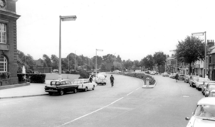 General view of a street in Nuneaton, with cars parked on both sides of the road.  1960s |  IMAGE LOCATION: (Warwickshire County Record Office)