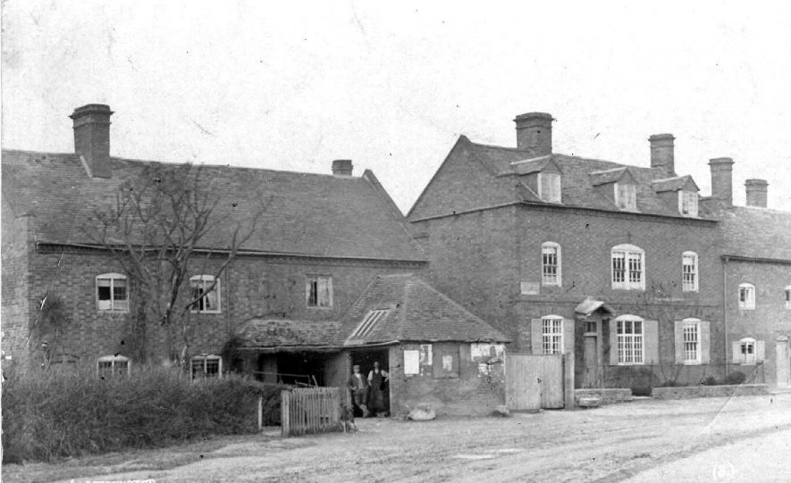 Cottages and houses with two workmen standing in an outhouse.  c.1905  [The picture shows the village Forge. The 'outhouse' on the front was where the blacksmith shoed the horses. It would be the blacksmith standing in the doorway. Over time the property have had windows added to the attic and the forge removed. The property next door was the village shop.] |  IMAGE LOCATION: (Warwickshire County Record Office)