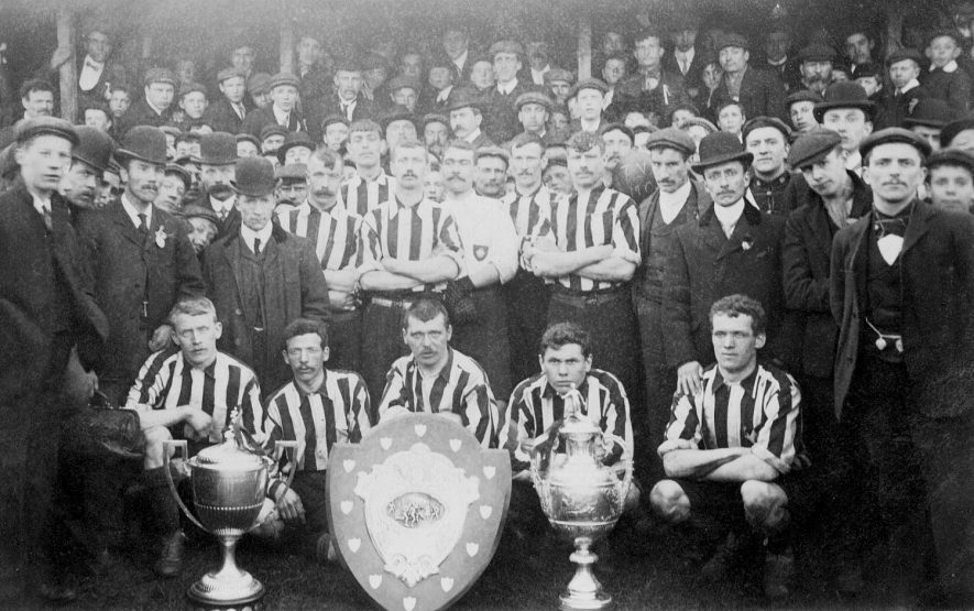 Atherstone Town Football Club.  A. Archer, goalkeeper.  Team, managers and supporters. Display of trophies.  1900s    IMAGE LOCATION: (Warwickshire County Record Office)